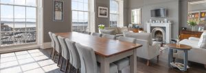Barnes hand made wooden furniture featuring a long wooden dining table with high back chairs