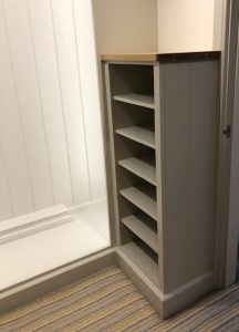 Handmade bespoke storage for dressing rooms showing a wooden rack for shoe storage